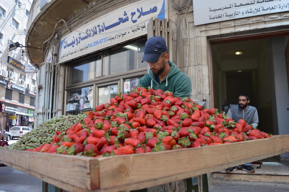 Ein Sicherheitsmann der Palästinensischen Autonomiebehörde (r.) in Ramallah vor einem Berg Erdbeeren (Foto: Til Biermann)